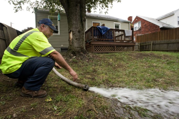 Lewis McDonald, chief engineer for the Strasburg Fire Department, directs  water from the basement of this Charles Street home that flooded on Wednesday afternoon.   Heavy rain is on the way, forecasters say. Rich Cooley/Daily
